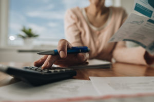 Close up of unrecognizable woman planning home budget and using calculator.